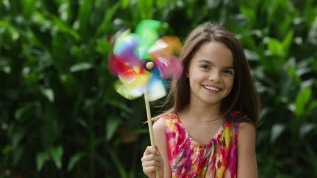 ms young girl holding a spinning pin wheel, smiling - windrad stock-videos und b-roll-filmmaterial