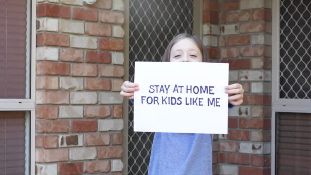 young girl holding stay at home sign - placard stock videos & royalty-free footage
