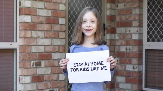 vídeos y material grabado en eventos de stock de joven chica que se mantiene en casa signo - refugiarse en un lugar concepto