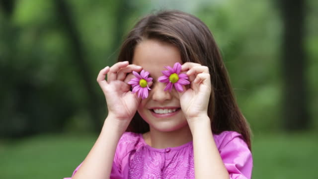 CU Young girl holds flowers over her eyes for fun then says Boo