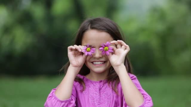 vídeos de stock, filmes e b-roll de ms young girl holds flowers over her eyes for fun - mãos cobrindo olhos