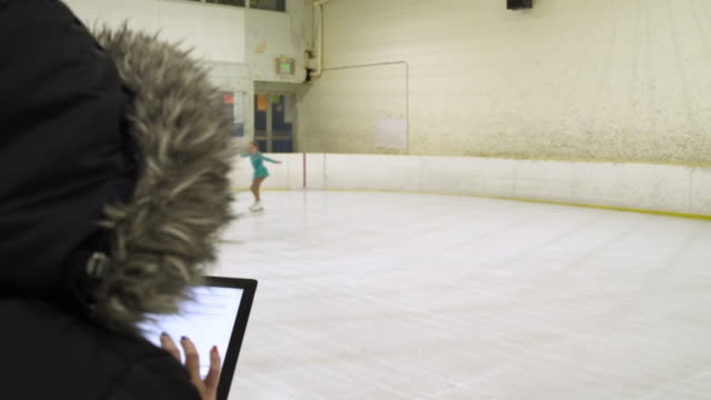 young girl ice skating on ice rink with woman using digital tablet. - figure skating stock videos and b-roll footage
