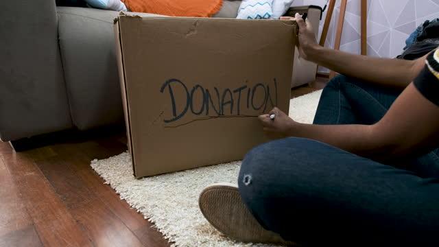 vídeos y material grabado en eventos de stock de niña que identifica la caja de la donación. - sólo mujeres jóvenes