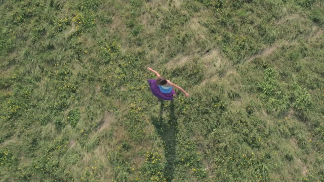 Young Girl in a Dress Spins in the Grass Outdoors