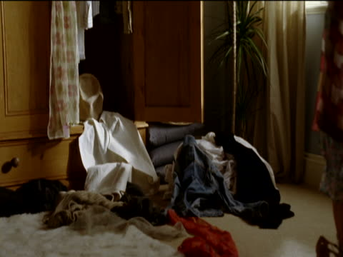 vidéos et rushes de young girl in a messy bedroom, wearing grown up clothes and looking in a mirror - messy bedroom