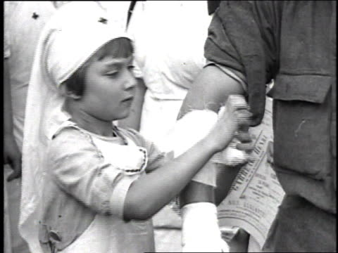 young girl in a nurse's uniform bandaging a soldier's arm very well / france - red cross stock videos & royalty-free footage