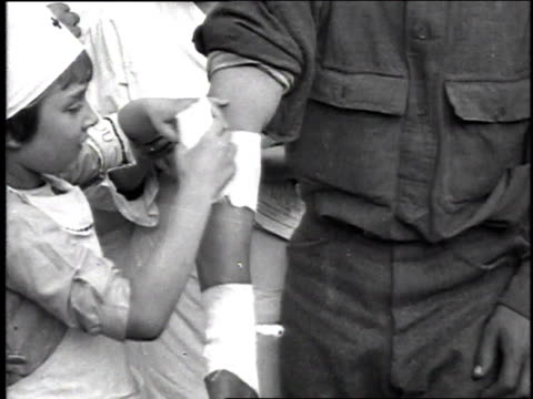 young girl in a nurse's uniform bandaging a soldier's arm very well / france - medical dressing stock videos & royalty-free footage