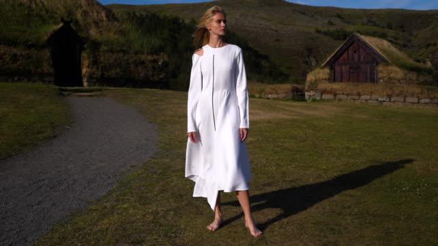 ung flicka i en forntida bosättning av folken på island. saga fashion story - gud bildbanksvideor och videomaterial från bakom kulisserna