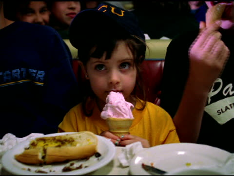 young girl in baseball cap eating pink ice cream in cone, pawtucket - baseball cap stock videos & royalty-free footage