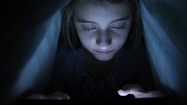Young Girl in Bed on a Tablet