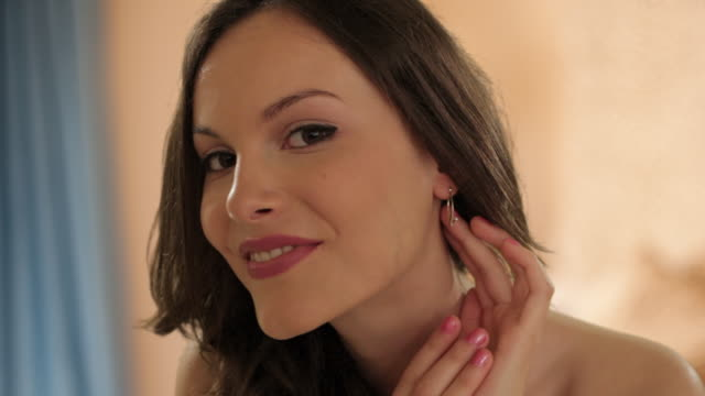 stockvideo's en b-roll-footage met young girl in bedroom trying earrings - oorbel