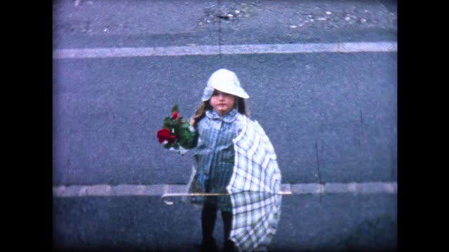 1965 young girl in blue rain coat, hat, holding roses
