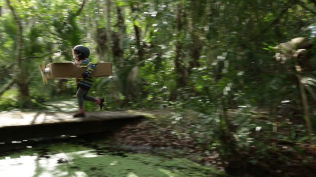 PAN Young girl in cardboard aeroplane running over bridge in woods, dressed as pilot.