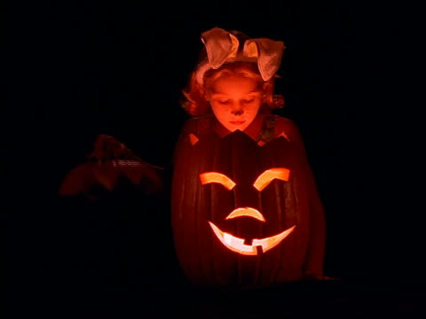 Young girl in costume looking into lit jack-o-lantern