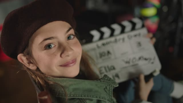 slo mo. young girl in director's chair smiles at camera while holding film slate with cameraman crossed out and woman written in all caps on a set with all female filmmakers. - ディレクター点の映像素材/bロール