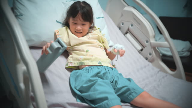 young girl in moody excited sitting on the bed in hospital - consoling stock videos & royalty-free footage