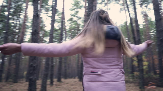 young girl in pink coat spinning around in autumn forest - only teenage girls stock videos & royalty-free footage