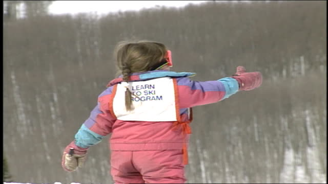 young girl in pink snowsuit with learners tag holding a woman's hand and skiing in butte colorado - スキーウェア点の映像素材/bロール
