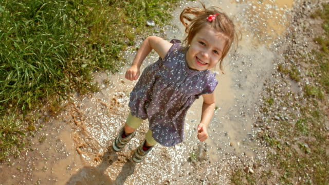 slo mo young girl in rain boots jumping up and down in the puddle and laughing - jumping stock videos & royalty-free footage