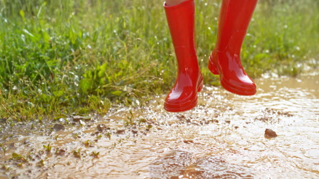 slo mo young girl in red rainboots jumping up and down in a muddy puddle - wellington boot stock videos & royalty-free footage