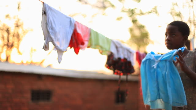 young girl in rural african village hanging up laundry - lavori domestici video stock e b–roll