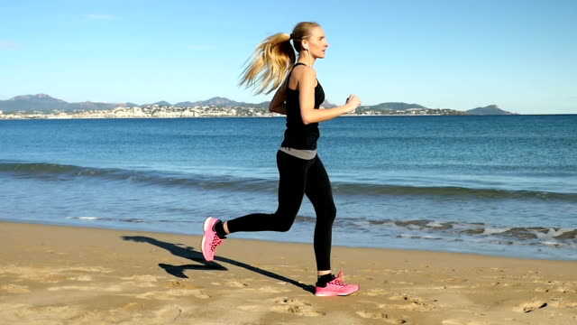 Young girl in sport outfit running along sea