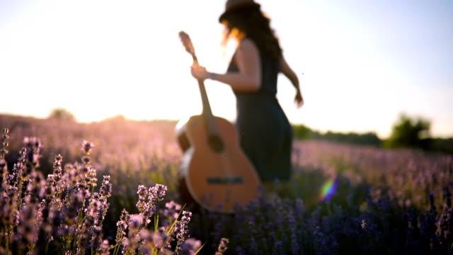 vidéos et rushes de jeune femme dans les champs de lavande - instrument de musique
