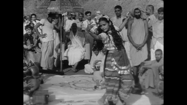 A young girl in traditional Indian costume dances outside before a gathered crowd