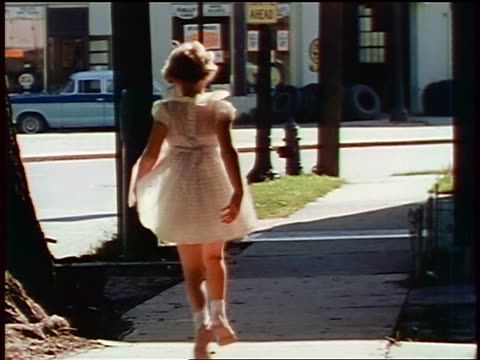 vídeos y material grabado en eventos de stock de 1957 rear view young girl in white dress skipping on suburban sidewalk / feature - 1957