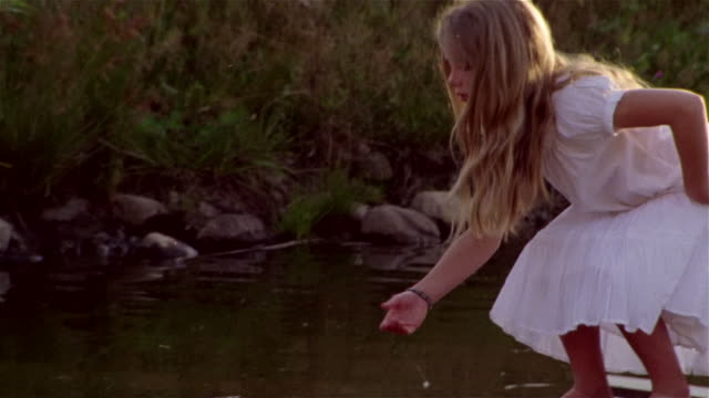 stockvideo's en b-roll-footage met young girl in white sundress standing on small wooden raft in pond reaching down and running hand along water / standing up, closing eyes and holding arms out to side - bukken