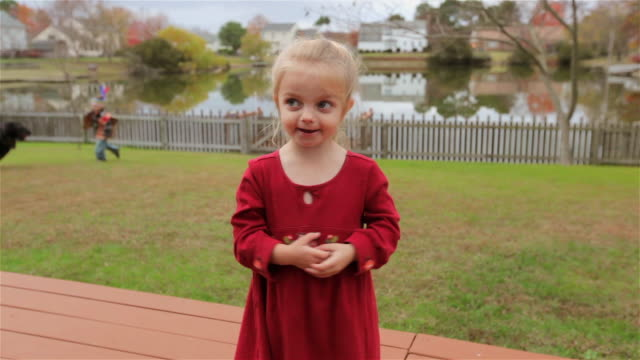 young girl innocently sings as her older brother chases the family dog around the backyard behind her - vignette stock videos & royalty-free footage