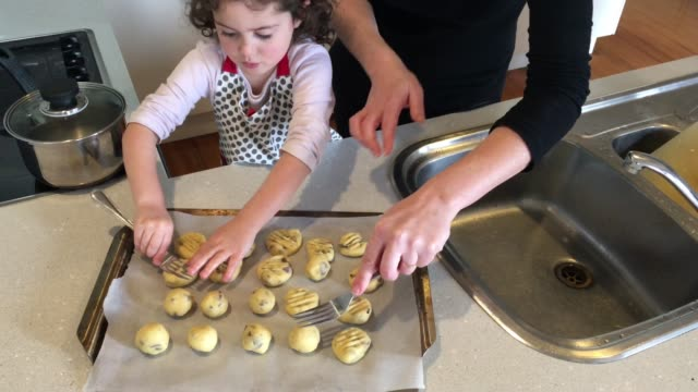 Young Girl is Baking Cookies with her Mother