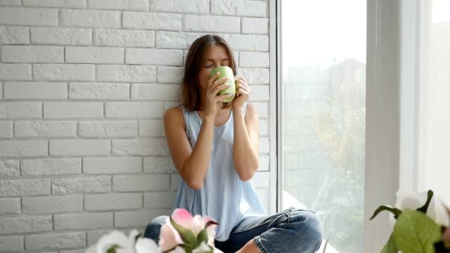 junges mädchen ist wirklich glücklich, während sie eine tasse kaffee trinken - ziegel stock-videos und b-roll-filmmaterial
