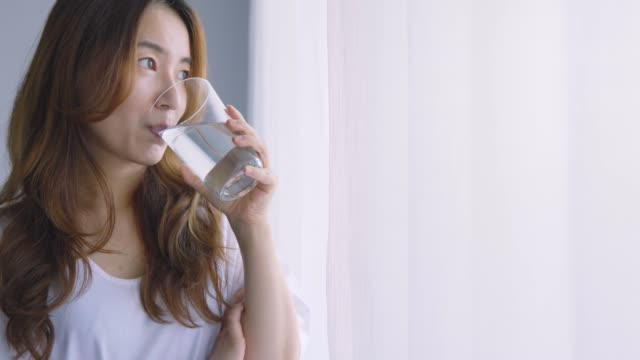 vidéos et rushes de jeune fille garde en bonne santé en buvant un verre d'eau - verre d'eau