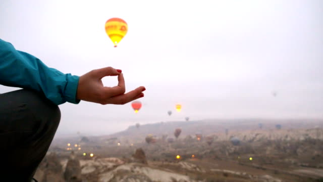 young girl is meditating while watching hot air balloons flying in goreme in cappadocia - photographer stock videos & royalty-free footage