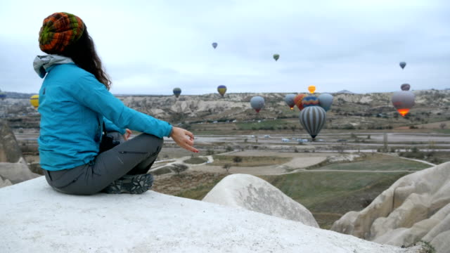 young girl is meditating while watching hot air balloons flying in red and rose valley in goreme in cappadocia in turkey - person cross legged stock videos & royalty-free footage