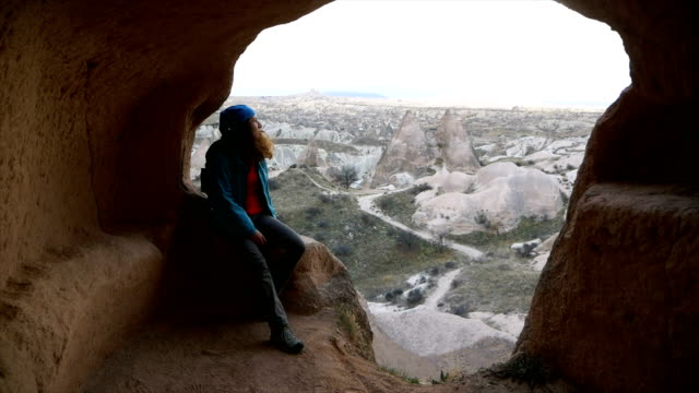 young girl is standing in cave house and  watching the  red and rose valley in cappadocia in goreme in turkey - rock hoodoo stock videos & royalty-free footage
