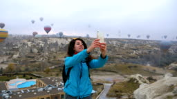 Young girl  is taking selfie photos of  herself while watching hot air balloons flying in Goreme in Cappadocia in Turkey