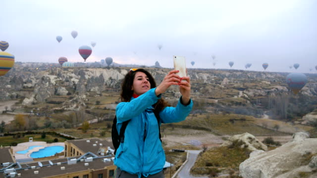 young girl  is taking selfie photos of  herself while watching hot air balloons flying in goreme in cappadocia in turkey - bright colour stock videos & royalty-free footage