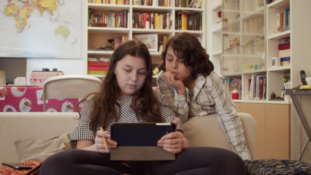 young girl is using a tablet sitting on the sofa at home together with her brother - table stock videos & royalty-free footage
