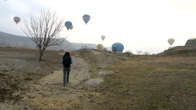 young girl is walking on rock hoodoo while watching hot air balloons flying in goreme in cappadocia in turkey - rock hoodoo stock videos & royalty-free footage