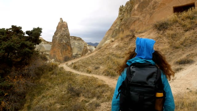 young girl is walking through red and rose valley cappadocia in goreme in turkey - rock hoodoo stock videos & royalty-free footage