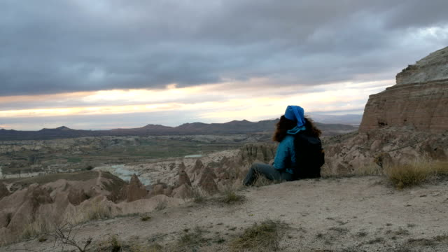 young girl is walking through red and rose valley cappadocia in goreme in turkey - rock hoodoo stock videos and b-roll footage