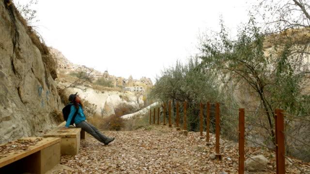 young girl is walking through the cappadocia guvercilik valley in goreme in turkey - rock hoodoo stock videos & royalty-free footage