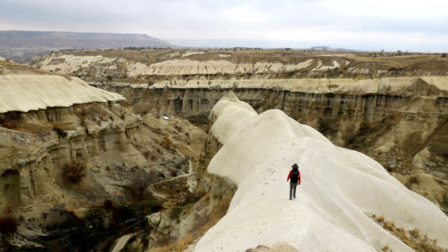young girl is walking through the cappadocia guvercilik valley in goreme in turkey - rock hoodoo stock videos and b-roll footage