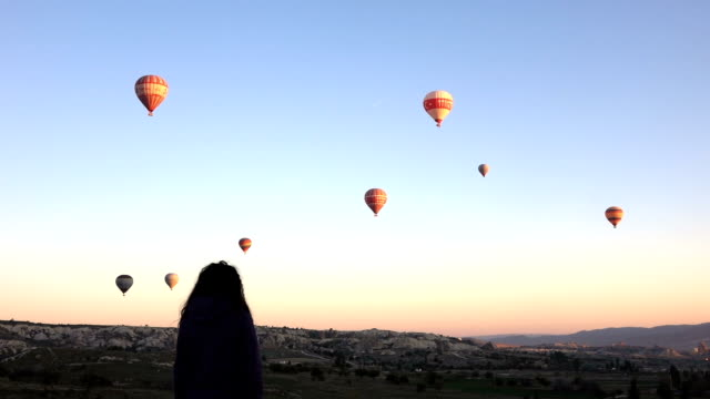 young girl is watching of hot air balloons flying over the goreme  in cappadocia - cappadocia stock videos and b-roll footage