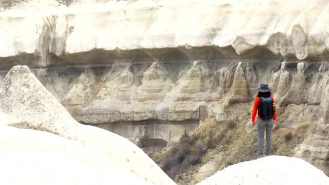 young girl is watching the  cappadocia guvercilik valley in goreme in turkey - rock hoodoo stock videos & royalty-free footage