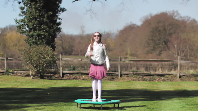 young girl jumping and dancing on trampoline in garden - pedana elastica per saltare video stock e b–roll