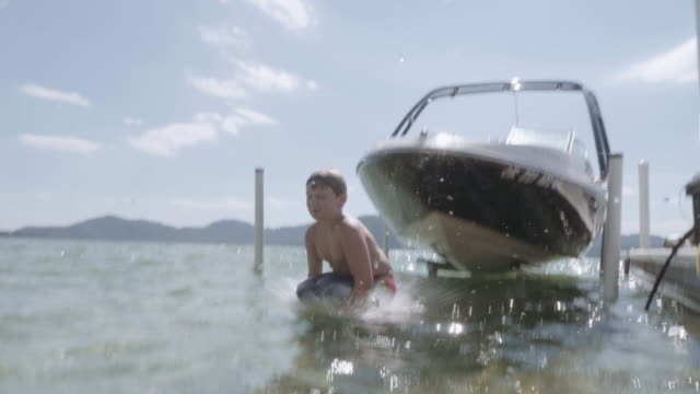 4K SLO MO: Young girl jumping off a ski boat into the water