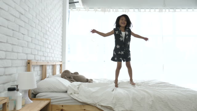 Young Girl Jumping On Bed, Slow motion